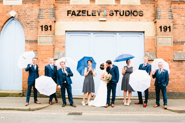 Wedding party with umbrellas outside Fazeley Studios by John Charlton Photography