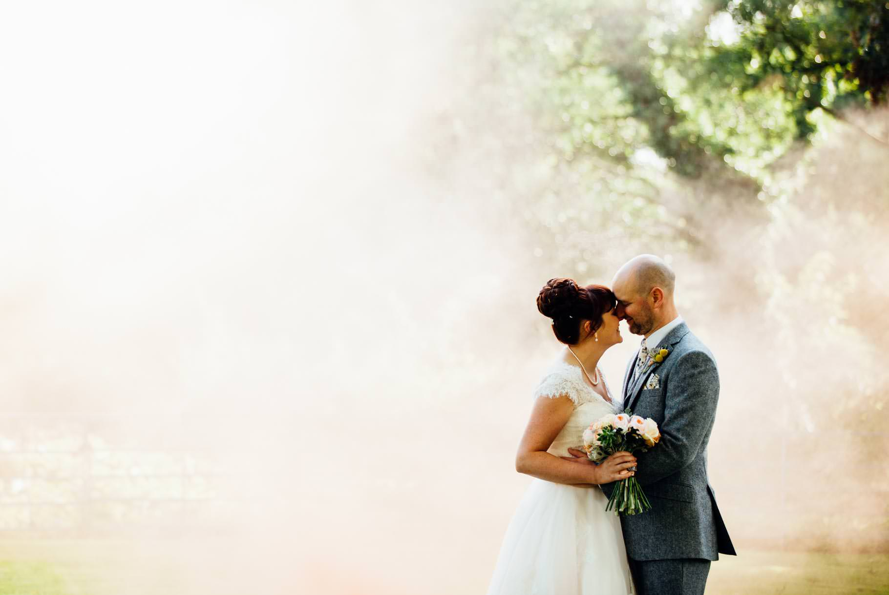 West Mill Derby wedding bride and groom in sunlight with background of smoke