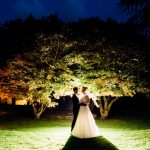 Hampton Manor wedding with bride and groom at night in front of trees