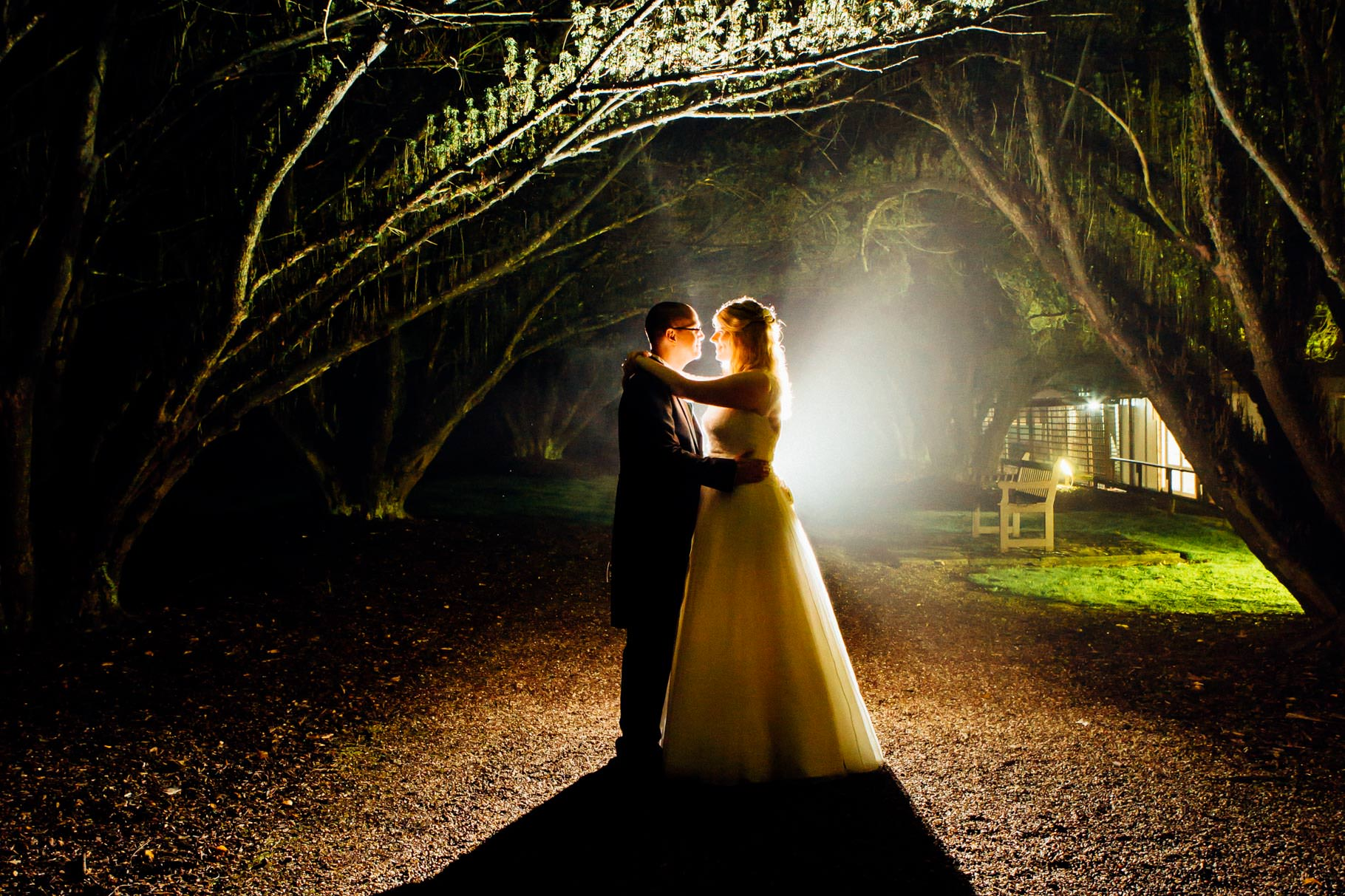 New Hall wedding bride and groom at night under arch of trees