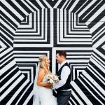 Bride and groom at Fazeley Studios wedding in front of a black and white wall of geometric shapes