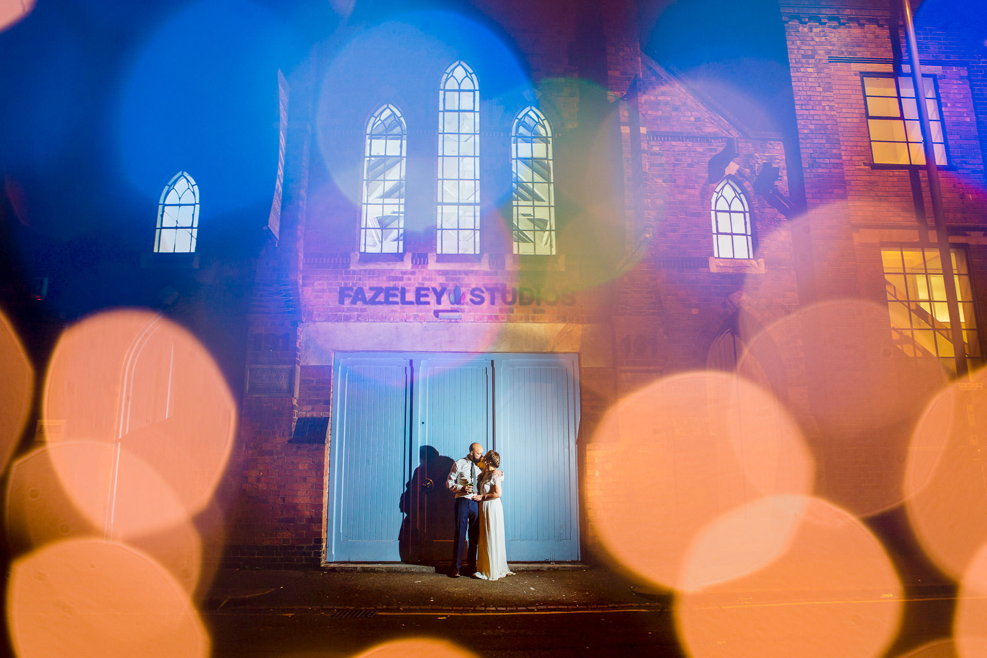 bride and groom standing in front of Fazeley Studios at night